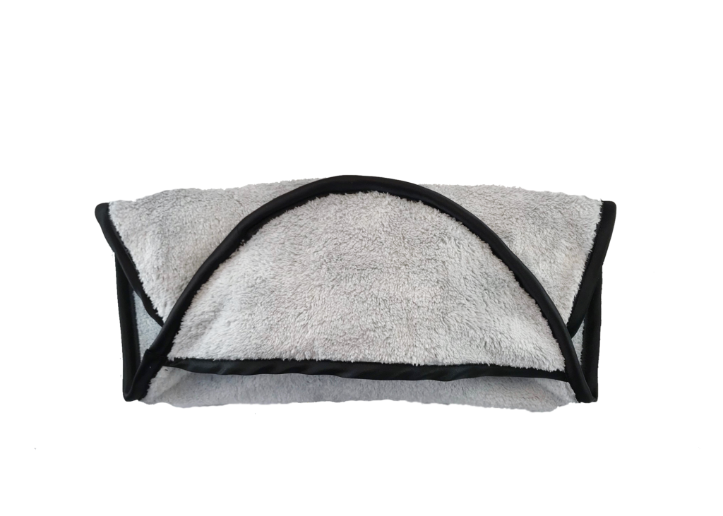 Photograph of The Cumpanion folded into thirds. It is a grey microfiber towel with a black edge.
